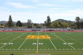 The renovated facilities, including the new gym floor (right) and the improved field came as a result of potential safety hazards to student athletes. [Bailey Cinelli]